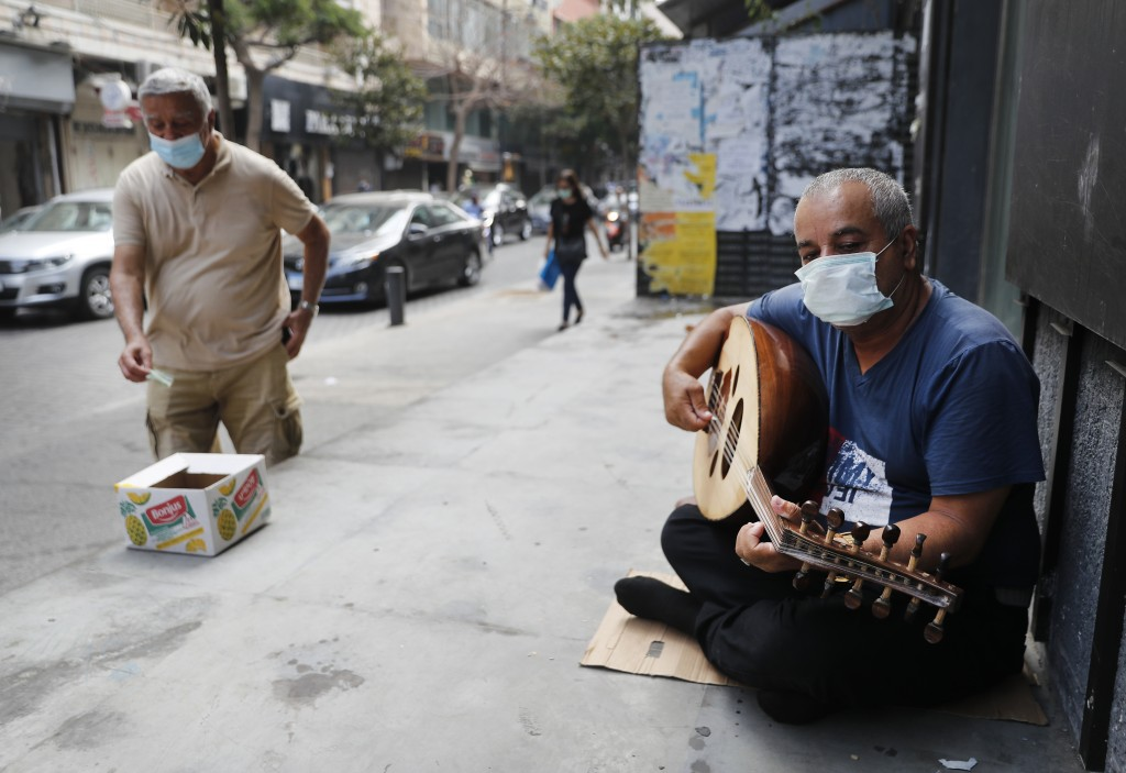 A street musician man performs with a mask on his face to help stop the spread of the coronavirus, as other man on the left puts money on a box, in Be...