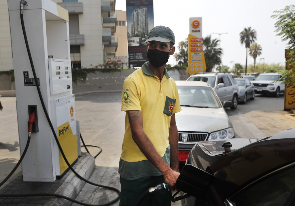 A gas station worker fills gasoline at a car, as other cars, background, line up amid fuel shortages, in Beirut, Lebanon, Wednesday, July 29, 2020.  L...