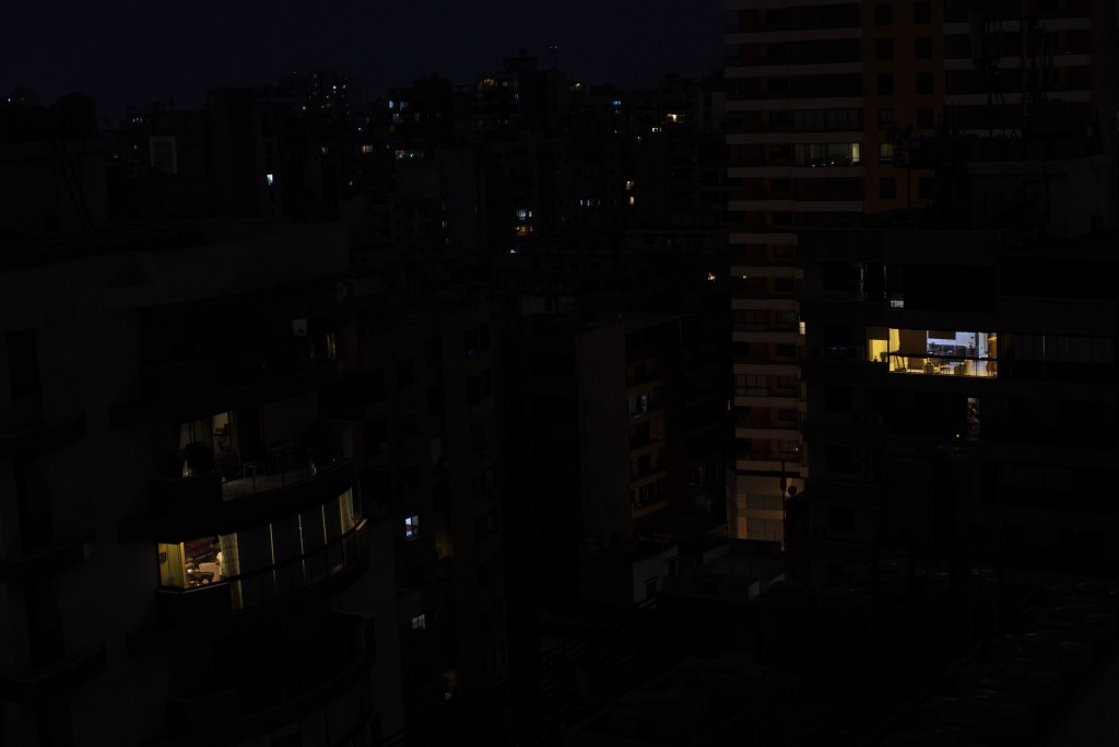 FILE - in this July 6, 2020 file photo, Lebanon's capital city of Beirut remains in darkness during a power outage. The multiple crises may seem like ...