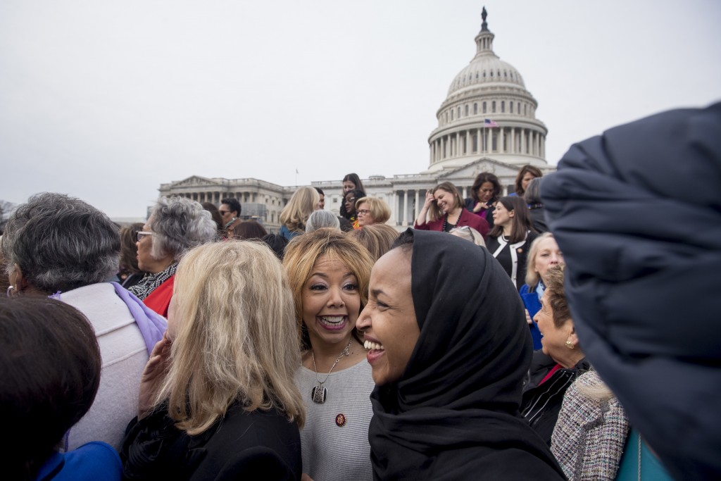 FILE - In this Friday, Jan. 4, 2019 file photo, Rep. Lucy McBath, D-Ga., center, smiles with Rep. Ilhan Omar, D-Minn., second from right, following a ...
