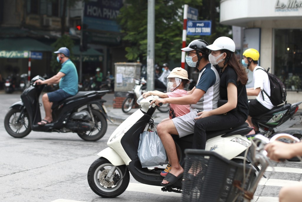 People wearing face masks ride motorcycles in Hanoi, Vietnam, Monday, Aug. 3, 2020.