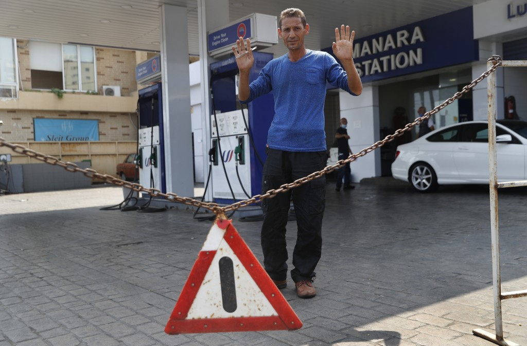 A gas station workers gestures as he saying no fuel at the station, in Beirut, Lebanon, Wednesday, July 29, 2020.  Lebanon is hurtling toward a tippin...