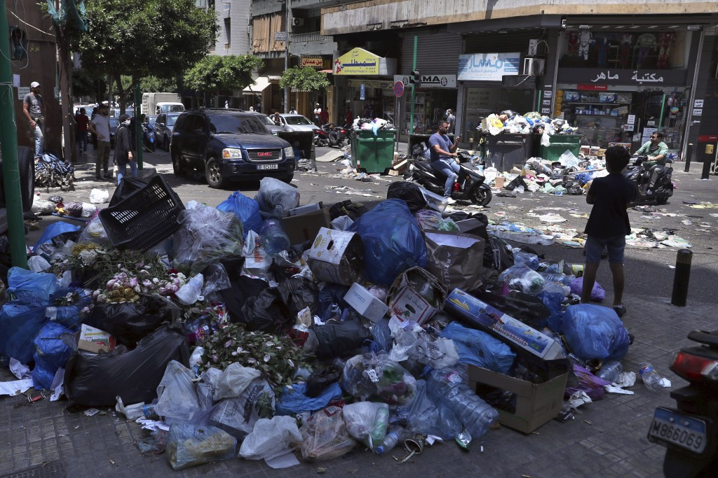 FILE - In this July 14, 2020 file photo, a road is partially blocked with garbage and bins in protest of uncollected trash, in Beirut, Lebanon.  Leban...