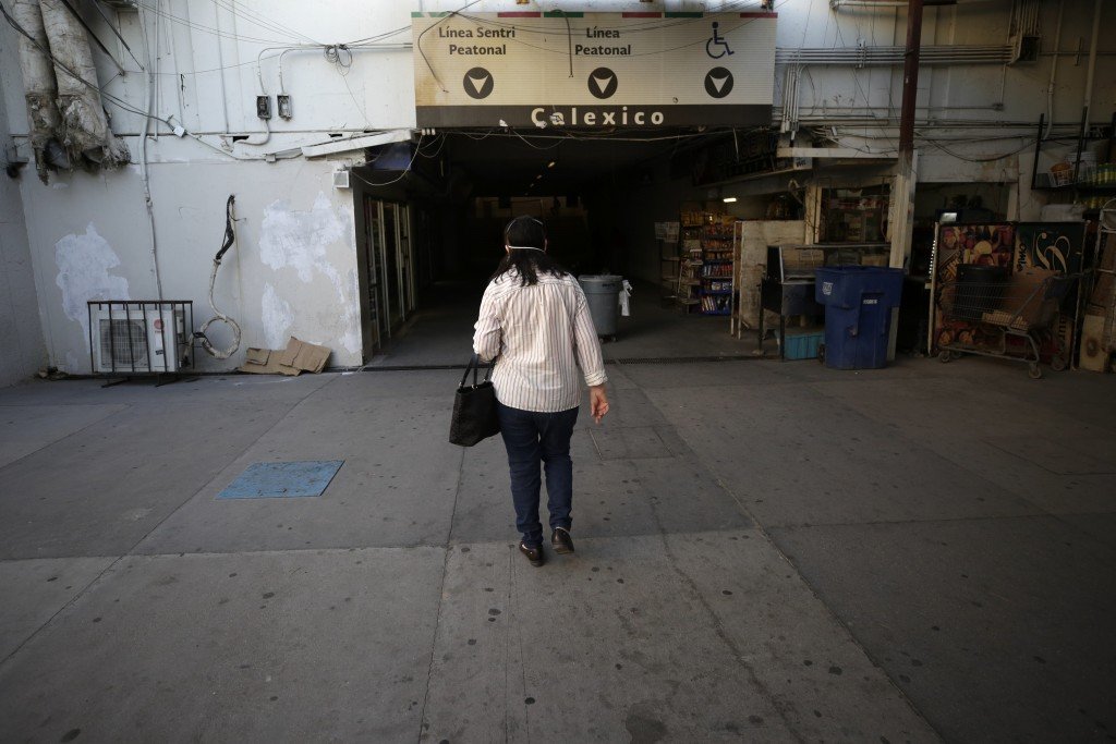 A woman walks along a tunnel on her way to cross the border from Mexicali, Mexico, to Calexico, Calif., Wednesday, July 22, 2020. (AP Photo/Gregory Bu...