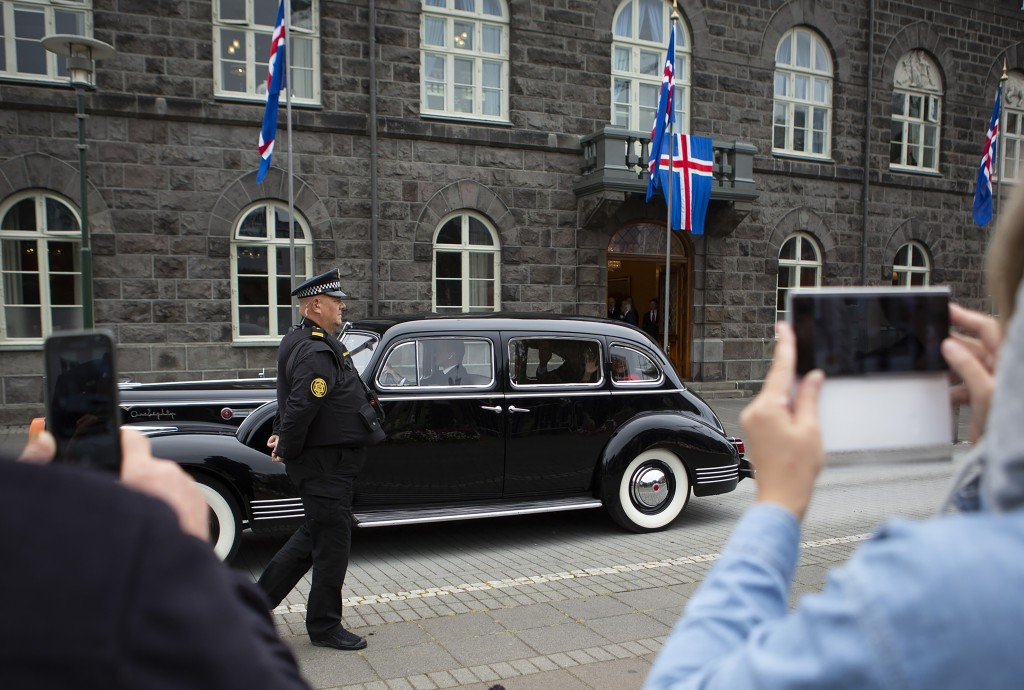 People take photos as Iceland's president Guðni Th. Jóhannesson is driven away in a car following his inauguration in Reykjavik, Iceland Saturday Aug....
