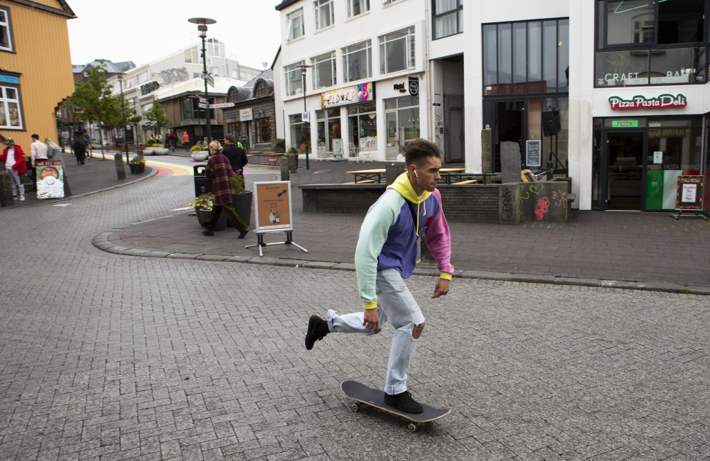 A skateboarder rides down a street in Reykjavik, Iceland Saturday Aug. 1, 2020. In Iceland, a nation so safe that its president runs errands on a bicy...