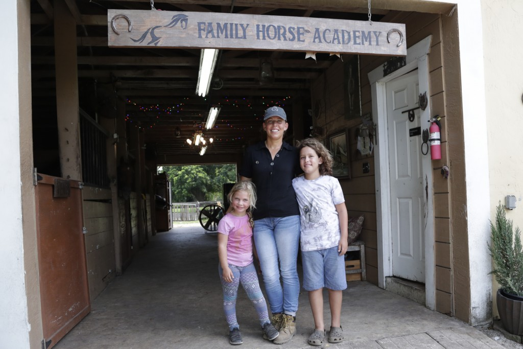 Timea Hunter poses for a photograph with her children Lena, left, and Liam, right, at the Family Horse Academy, where she is hoping to organize educat...