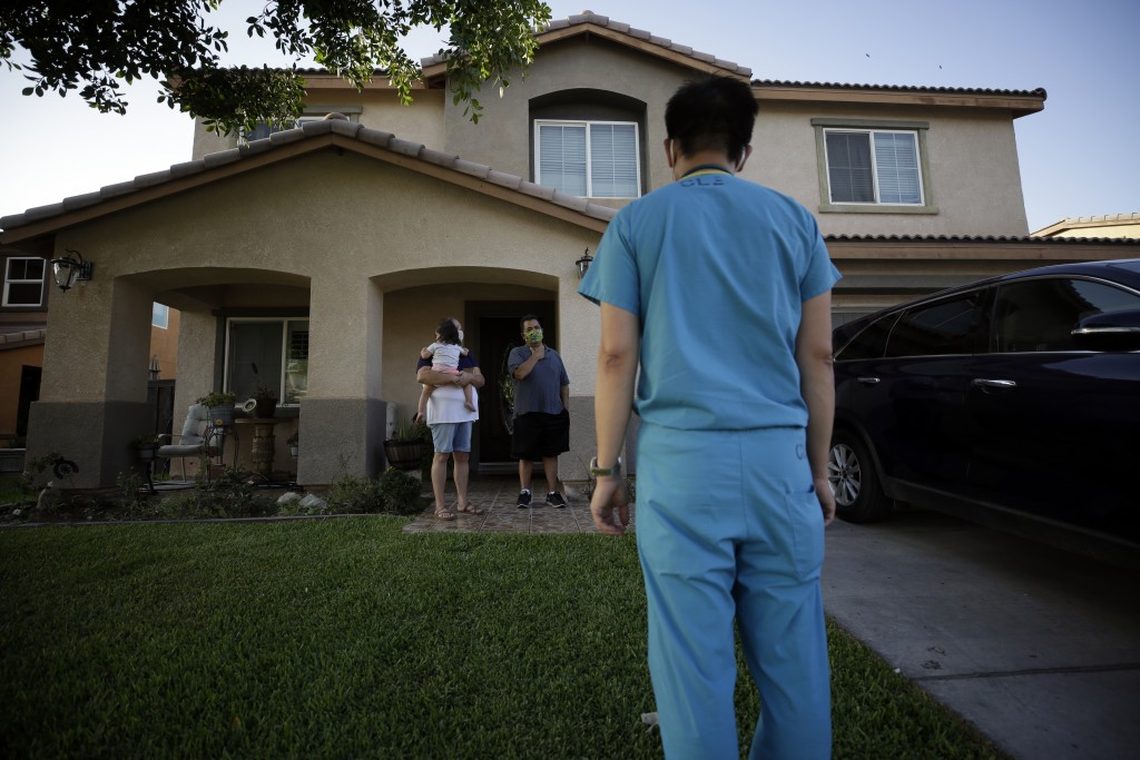 Dr. Tien Vo speaks to a family quarantining after testing positive for the coronavirus Thursday, July 23, 2020, in Calexico, Calif. Vo and members of ...