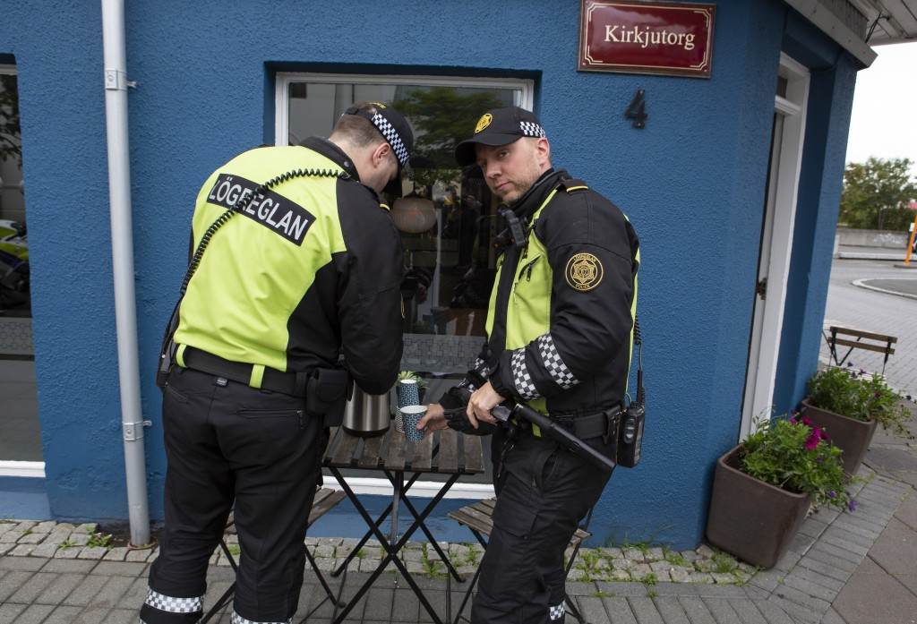 Two police officers help themselves to free coffee after standing guard outside the inauguration of Iceland's president Guðni Th. Jóhannesson in Reykj...