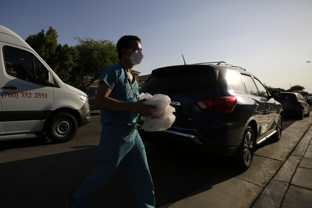 Dr. Tien Vo carries food for a family quarantining after testing positive for the coronavirus Thursday, July 23, 2020, in Calexico, Calif. Vo moved to...