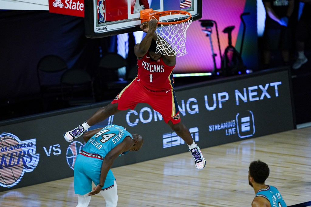 New Orleans Pelicans' Zion Williamson (1) comes down after a dunk over Memphis Grizzlies' Anthony Tolliver (44) during the first half of an NBA basket...