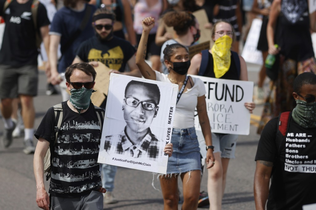 FILE - In this June 27, 2020 file photo, demonstrators carry placards as they walk down Sable Boulevard during a rally and march over the death of Eli...