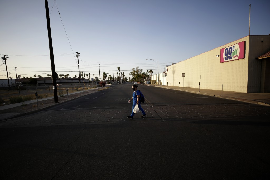 Dulce Garcia carries groceries as she makes her way home to Mexico after work Wednesday, July 22, 2020, in Calexico, Calif. (AP Photo/Gregory Bull)