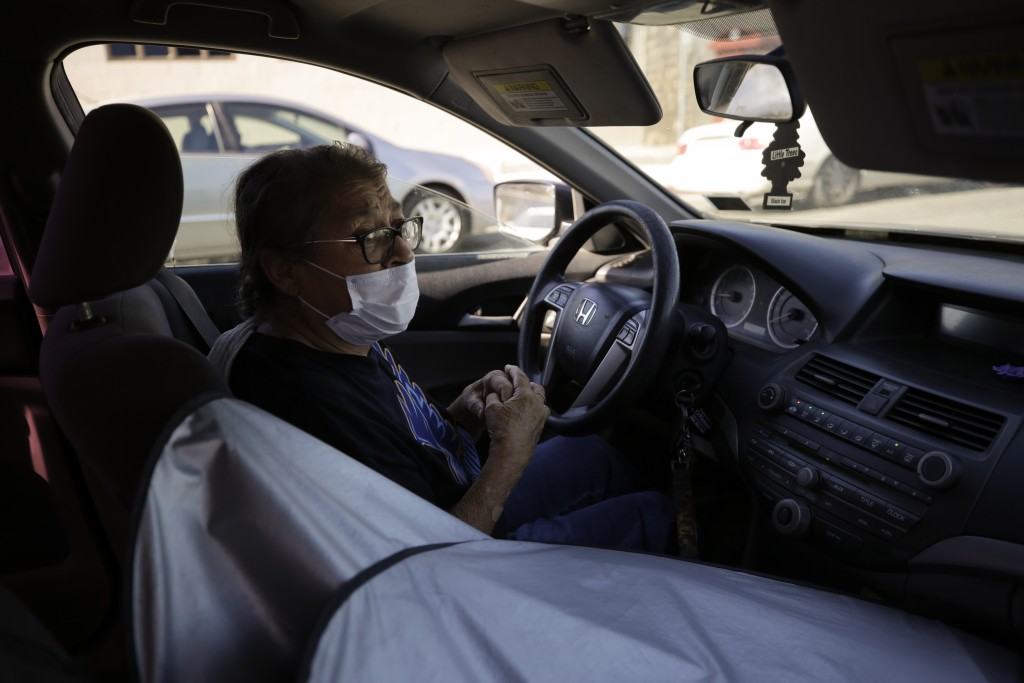 Marta Rosales waits in line for food at a distribution center Thursday, July 23, 2020, in Brawley, Calif. Rosales, who suffers from various health iss...