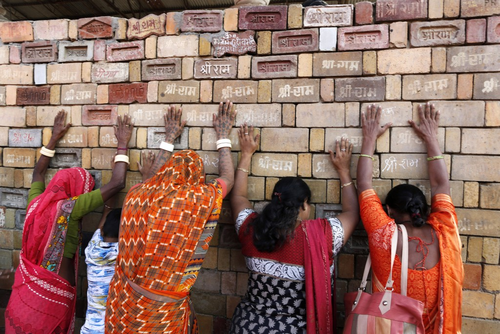 """FILE - In this Nov. 11, 2019, file photo, Hindu women devotees pray to the bricks reading """"Shree Ram"""" (Lord Ram), which are expected to be used in con..."""
