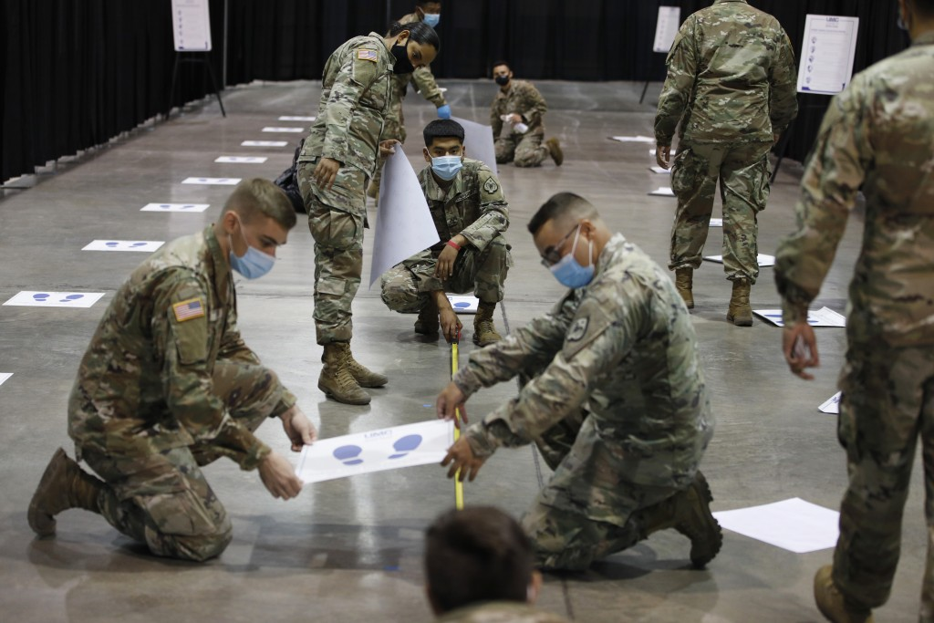 Members of the Nevada National Guard install social distancing stickers while setting up a new temporary coronavirus testing site Monday, Aug. 3, 2020...