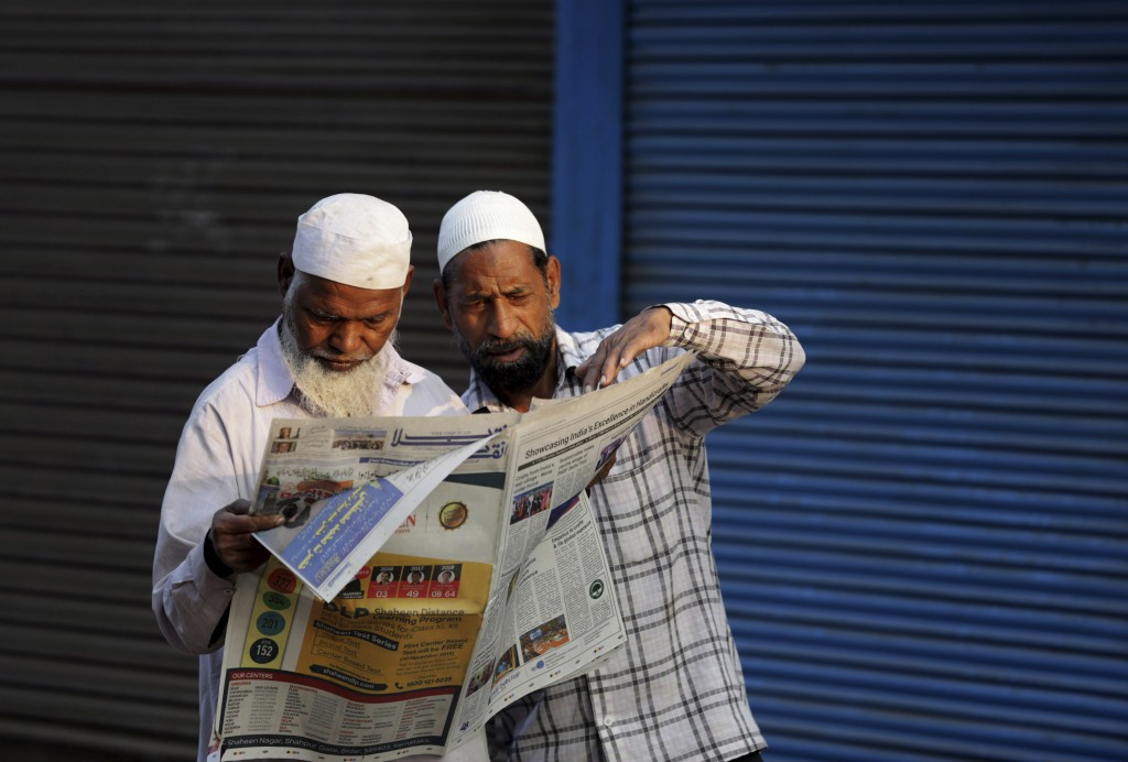 FILE - In this Nov. 10, 2019, file photo, Indian Muslims read a newspaper reporting about a Supreme Court verdict favoring the building of a Hindu tem...