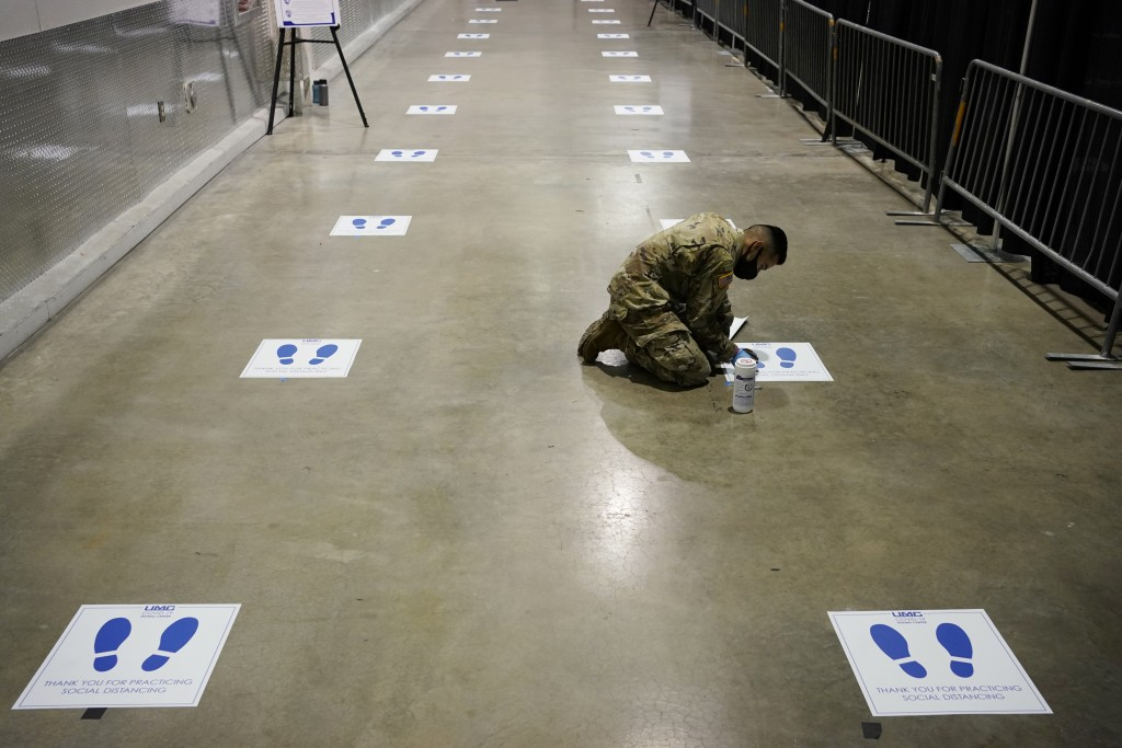 A member of the Nevada National Guard installs social distancing stickers while setting up a new temporary coronavirus testing site Monday, Aug. 3, 20...