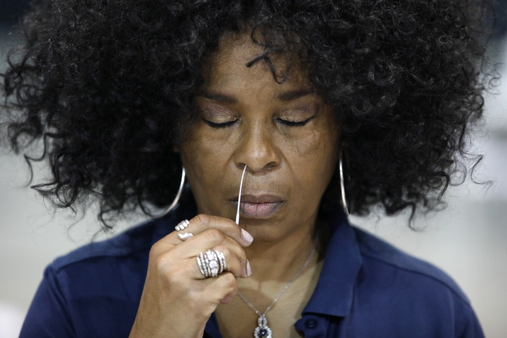 Rustye Barzoni Covington swabs her nose while giving a coronavirus test to herself during a tour of setup at a temporary coronavirus testing site Mond...