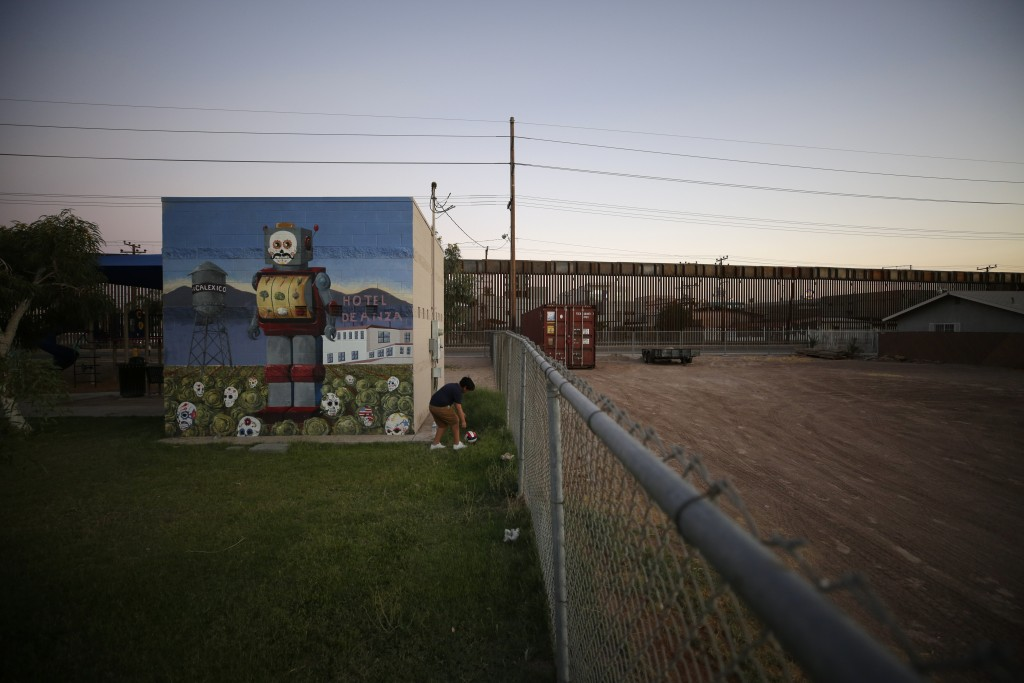 Gilberto Gil picks up a ball in a park as the border wall that separates Mexicali, Mexico from Calexico, Calif., sits in the distance, Tuesday, July 2...