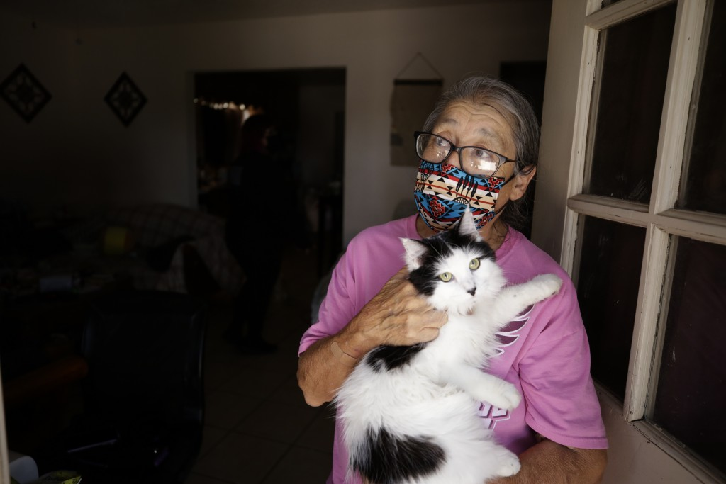 Marta Rosales holds her cat as she looks out from her house Thursday, July 23, 2020, in Brawley, Calif. Rosales stays home as much as possible to keep...