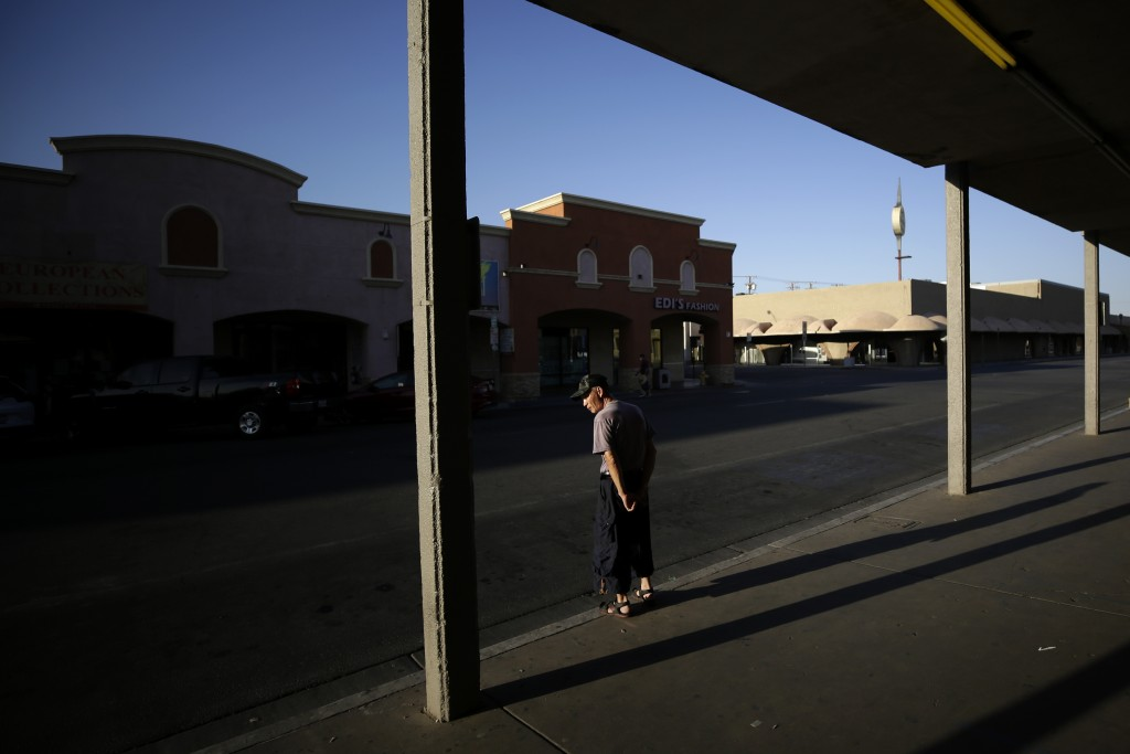 Clothing store owner Teeyung Chang looks out on empty streets Tuesday, July 21, 2020, in Calexico, Calif. Forced to shut his doors to shoppers as the ...