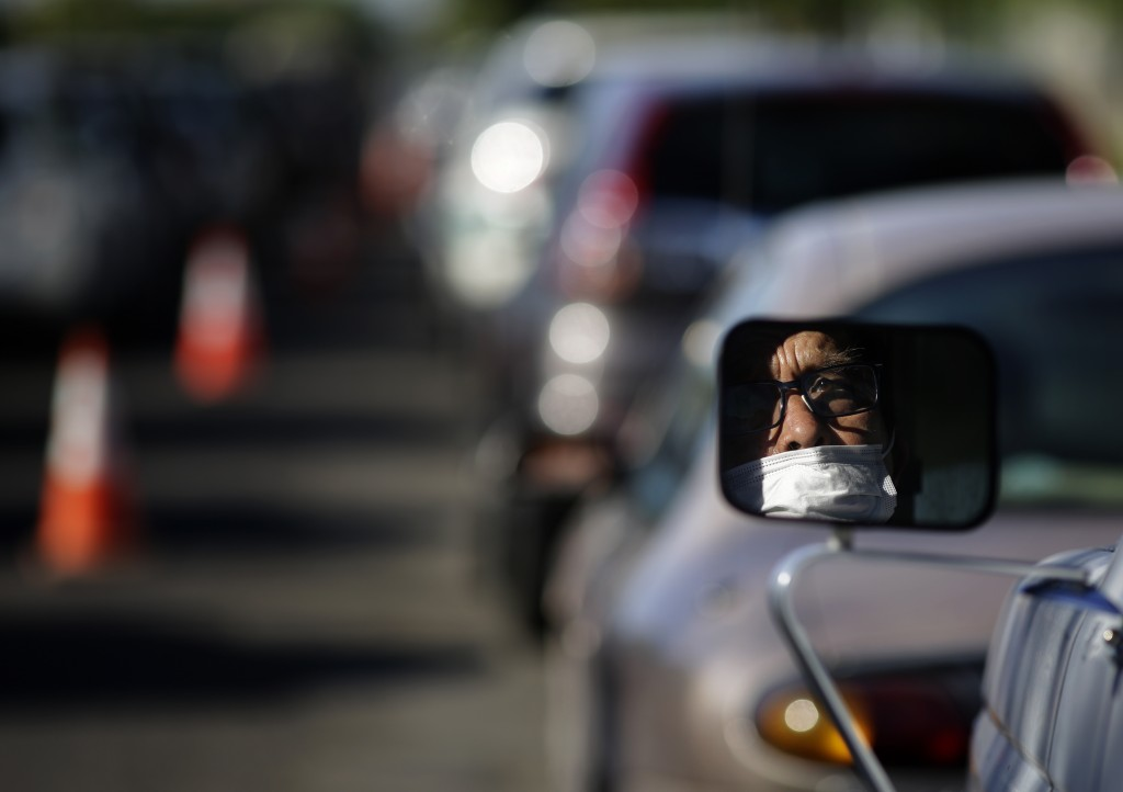 Guadalupe Guillen waits in line for food at a distribution center Thursday, July 23, 2020, in Brawley, Calif. Imperial County's poverty rate of 21% is...