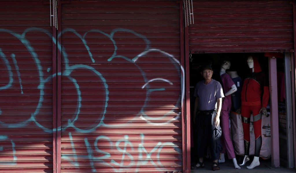 Teeyung Chang looks out the door of his shuttered clothing store near the border Tuesday, July 21, 2020, in Calexico, Calif. Forced to shut his doors ...