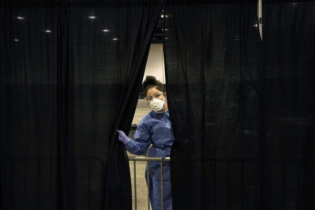 Diana Vega, a registered respiratory therapist, peeks through a curtain during setup at a temporary coronavirus testing site Monday, Aug. 3, 2020, in ...