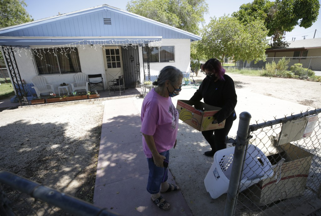 Marta Rosales, left, looks on as her daughter Erica Rosales takes a box of donated food from a neighbor into their house Thursday, July 23, 2020, in B...