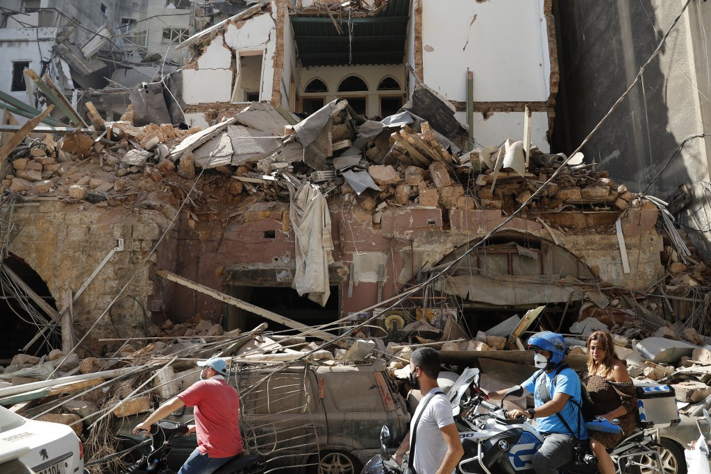 Citizens ride their scooters and motorcycles pass in front of a house that was destroyed in Tuesday's massive explosion in the seaport of Beirut, Leba...