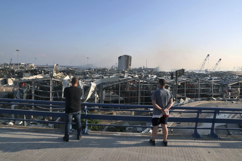 Men look at the scene of an explosion that hit the seaport of Beirut, Lebanon, Wednesday, Aug. 5, 2020. A massive explosion rocked Beirut on Tuesday, ...