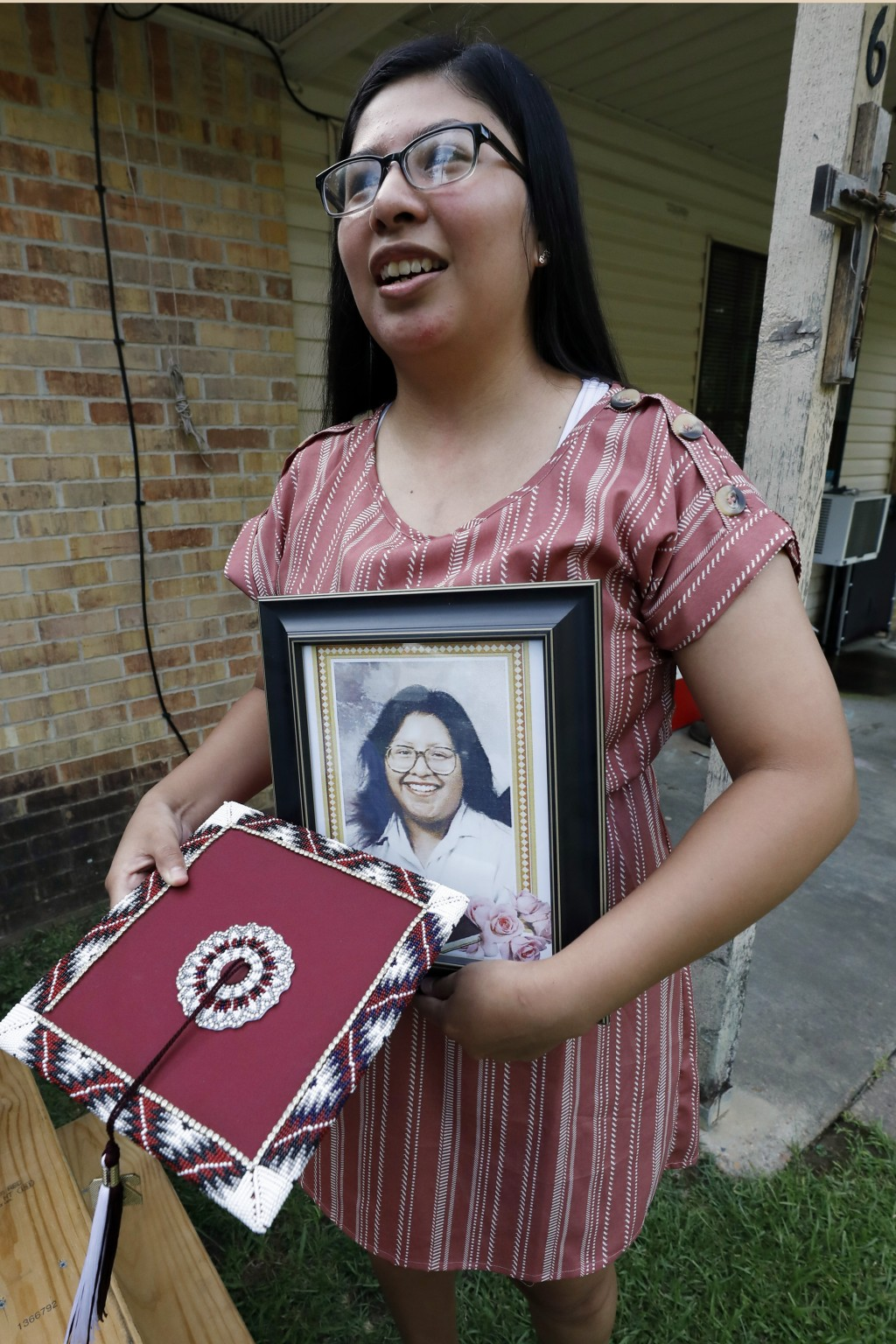 Kristina Taylor, 18, holds a portrait of her late mother, Sharon Taylor, and the special beaded mortar board she would have worn during graduation cer...