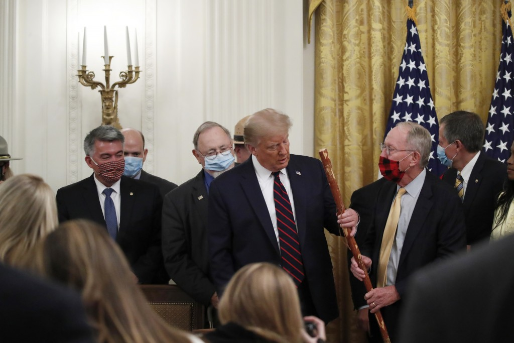 """Sen. Lamar Alexander, R-Tenn., gives President Donald Trump a walking stick during a signing ceremony for H.R. 1957 – """"The Great American Outdoors Act..."""