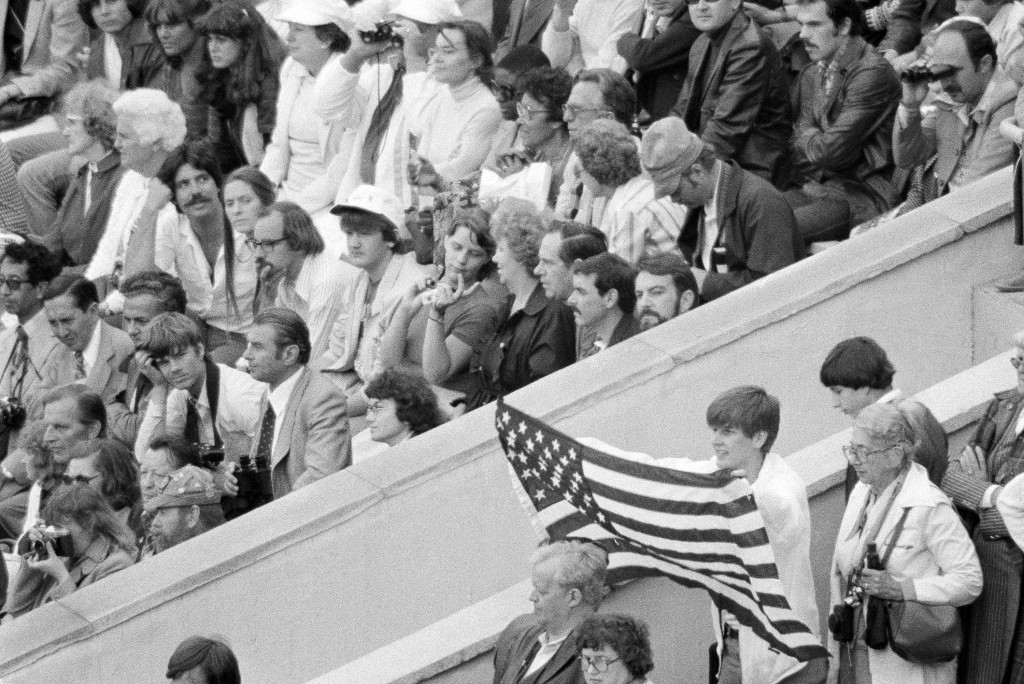 FILE - In this July 19, 1980, file photo, an unidentified youth displays the flag of the United States during opening ceremonies at the Summer Olympic...
