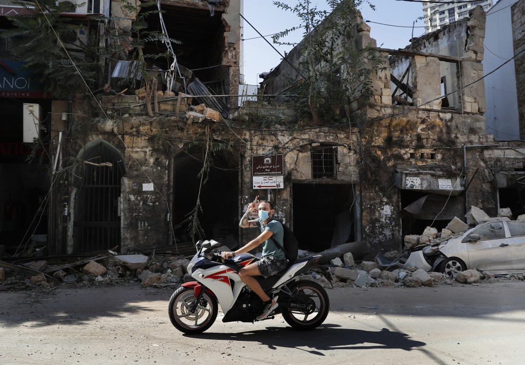 A man rides his motorcycle flashing a victory sign while passing a house destroyed by Tuesday's massive explosion in the seaport of Beirut, Lebanon, W...