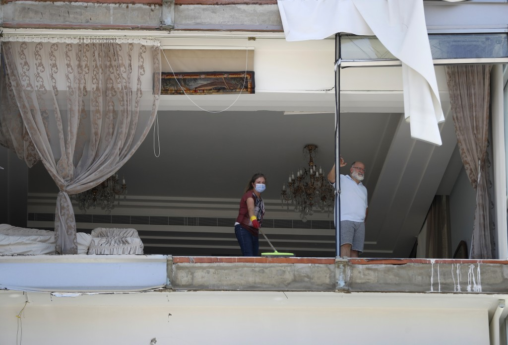 A woman cleans debris from her damaged apartment a day after an explosion hit the seaport of Beirut, Lebanon, Wednesday, Aug. 5, 2020. Residents of Be...