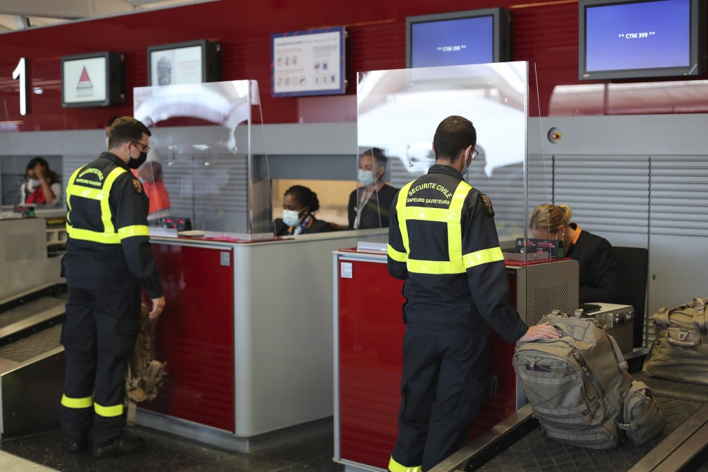 Members of the Securite Civile rescue organisation wait at the boarding desk at Charles de Gaulle airport, north of Paris, Wednesday, Aug.5, 2020. Fra...
