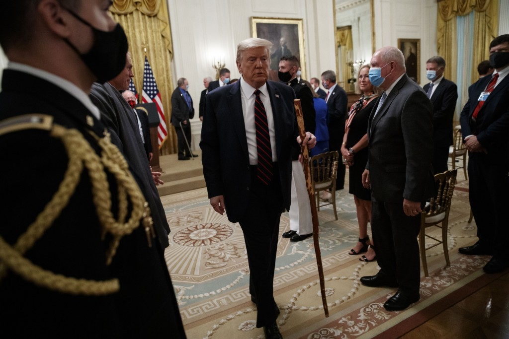 """President Donald Trump departs carrying a walking stick given to him by Sen. Lamar Alexander, R-Tenn., after a signing ceremony for H.R. 1957 – """"The G..."""