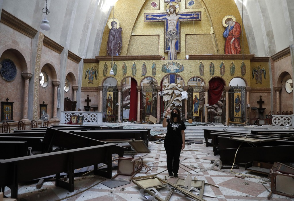 A woman takes pictures by her mobile phone for a damaged church, after an explosion hit the seaport of Beirut, Lebanon, Wednesday, Aug. 5, 2020. Resid...