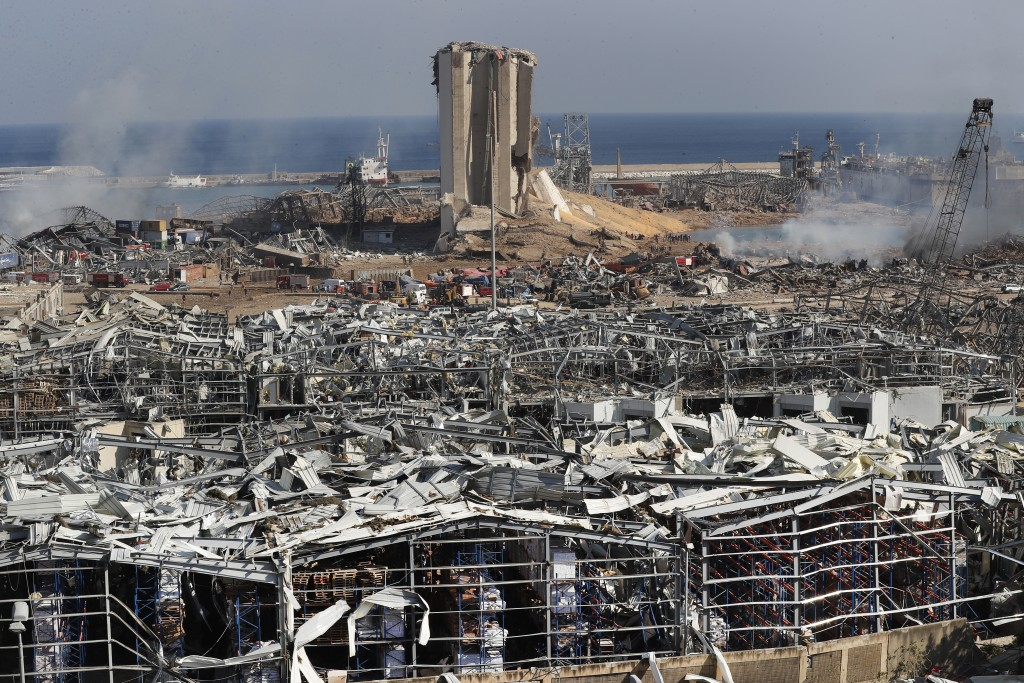 Rescue workers and security officers work at the scene of an explosion that hit the seaport of Beirut, Lebanon, Wednesday, Aug. 5, 2020. Prime Ministe...