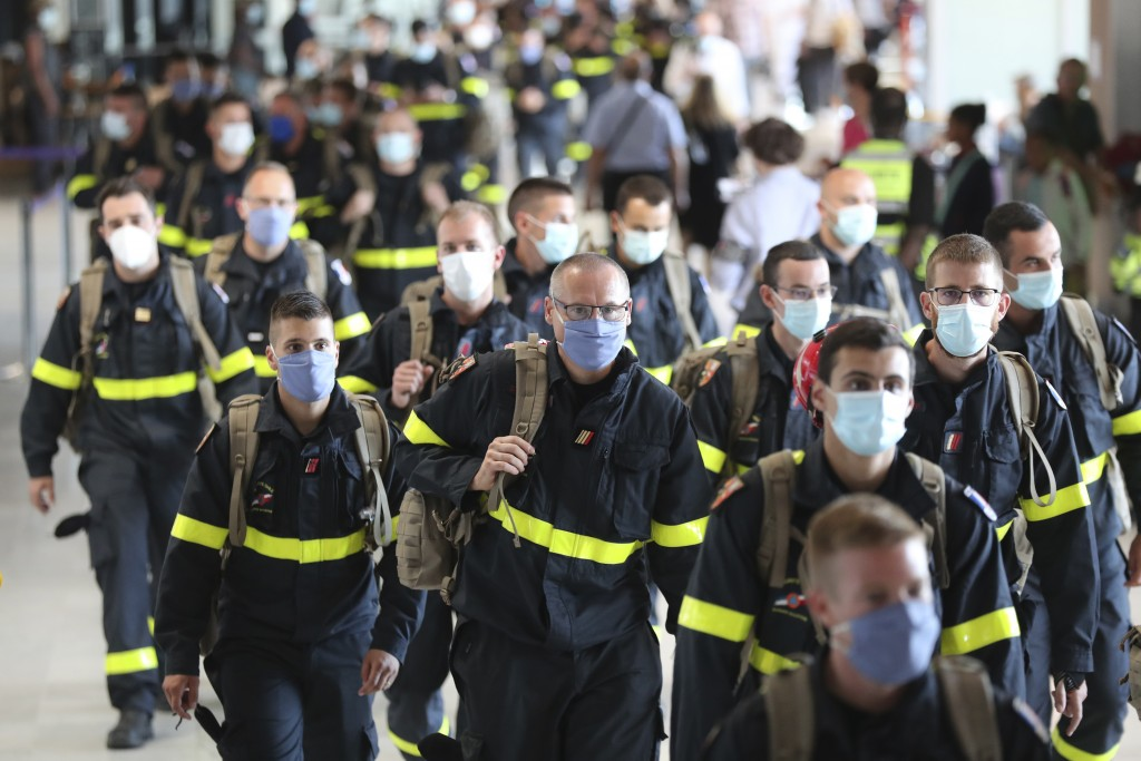 Members of the Securite Civile rescue organisation arrive at Charles de Gaulle airport, north of Paris, Wednesday, Aug.5, 2020. France is sending two ...