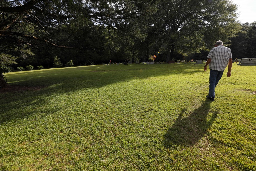 Father Bob Goodyear strolls across the center section of the cemetery on the grounds of the Holy Rosary Indian Mission in Tucker, Miss., Tuesday, July...