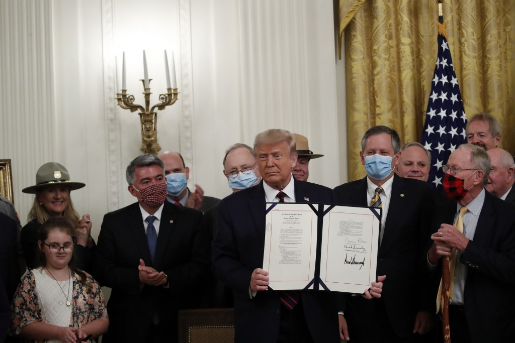 """President Donald Trump poses for a photo during a signing ceremony for H.R. 1957 – """"The Great American Outdoors Act,"""" in the East Room of the White Ho..."""