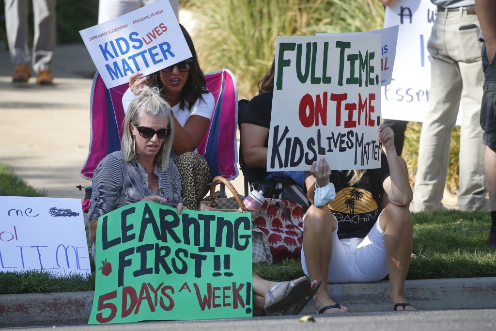Staci Patrick, left, protests with others in front of the Davis School District Office, Tuesday, Aug. 4, 2020, in Farmington, Utah. A group of parents...