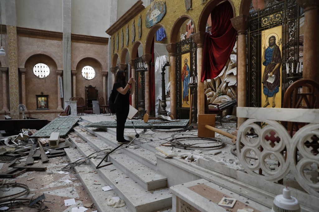 A woman takes pictures ofr a damaged church a day after an explosion hit the seaport of Beirut, Lebanon, Wednesday, Aug. 5, 2020. Residents of Beirut ...