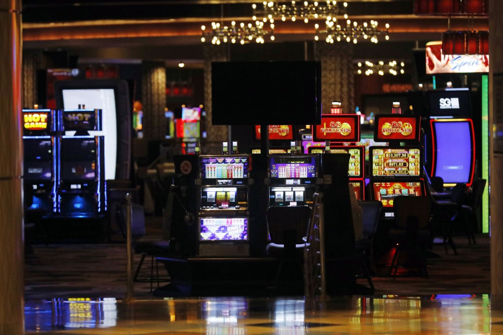 Brightly lit slot machines beckon players who cannot enter the closed gaming venues on the tribal lands of the Mississippi Band of Choctaw Indians in ...