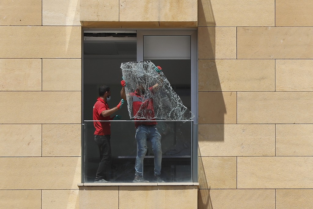 Workers throw a broken window from a damaged apartment a day after an explosion hit the seaport of Beirut, Lebanon, Wednesday, Aug. 5, 2020. Residents...