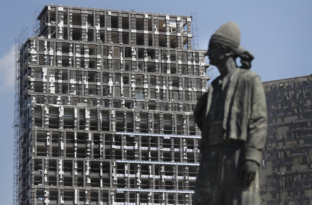 A statue representing the Lebanese expatriate is seen in front of a building that was damaged by an explosion that hit the seaport of Beirut, Lebanon,...