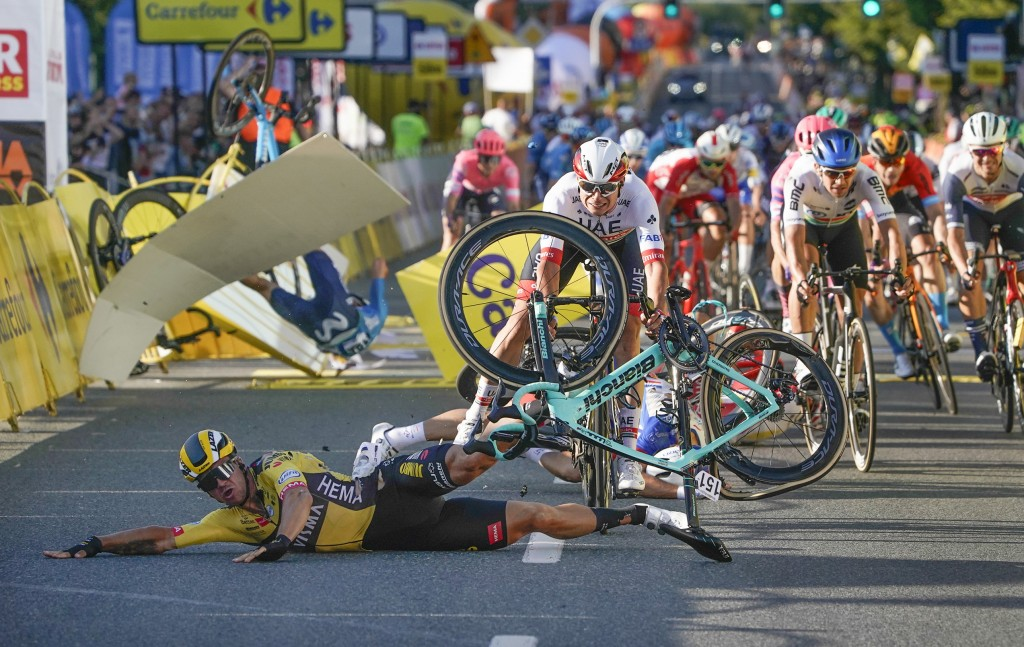 Dutch cyclist Dylan Groenewegen crashes to the ground as a bicycle is flying overhead in a major collision on the final stretch of the opening stage o...